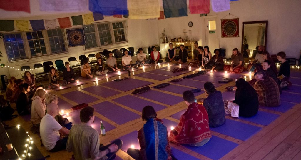 Psychedelic Yoga - People in a circle around the yoga mats